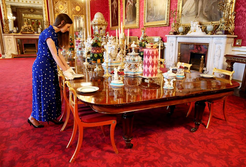 A Royal Collection employee adjusts placings at a recreation of a Victorian dinner in the State Dining Room at the exhibition to mark the 200th anniversary of the birth of Queen Victoria for the Summer Opening of Buckingham Palace, London. (Photo by Jonathan Brady/PA Images via Getty Images)