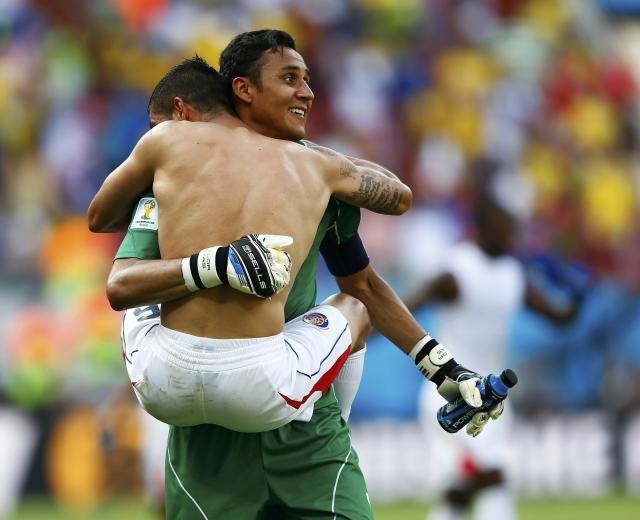 Costa Rica's goalkeeper Keilor Navas (back) and teammate Oscar Duarte celebrate defeating Italy at the end of their 2014 World Cup Group D soccer match at the Pernambuco arena in Recife June 20, 2014. REUTERS/Dominic Ebenbichler (BRAZIL - Tags: SOCCER SPORT WORLD CUP TPX IMAGES OF THE DAY) TOPCUP