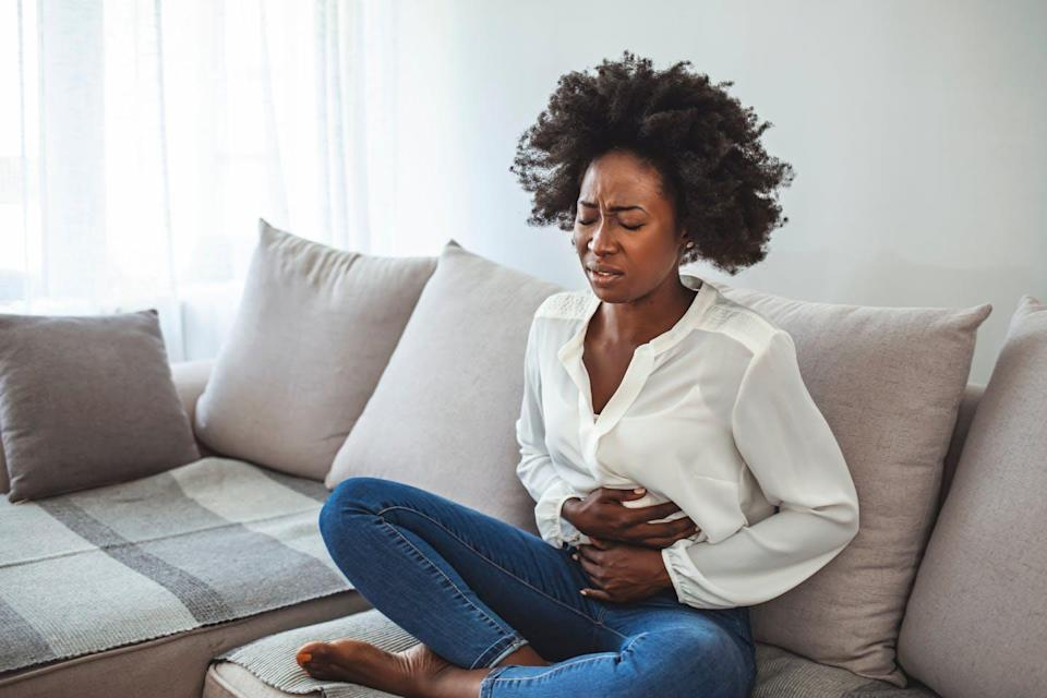 A woman sits on a sofa holding her stomach in pain