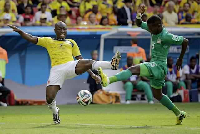 Colombia's Pablo Armero, left, and Ivory Coast's Max Gradel battle for the ball during the group C World Cup soccer match between Colombia and Ivory Coast at the Estadio Nacional in Brasilia, Brazil, Thursday, June 19, 2014. (AP Photo/Sergei Grits)