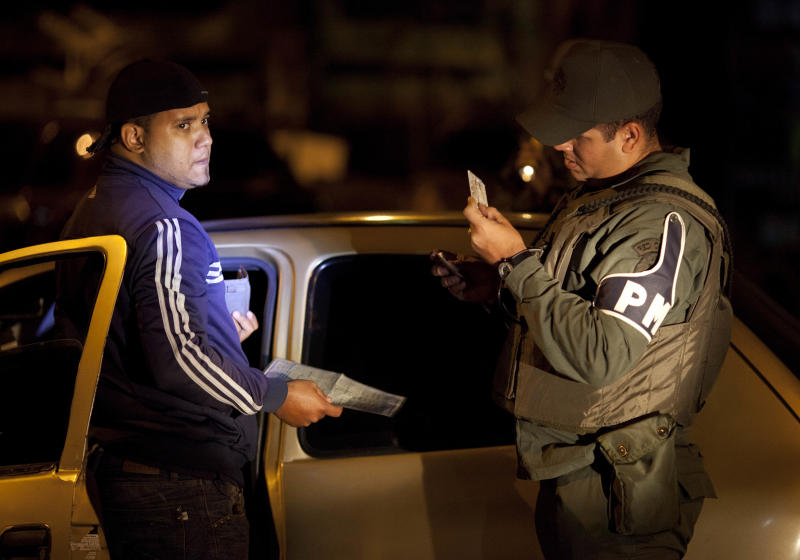 """In this May 14, 2013 photo, a National Guard soldier checks a driver's vehicle documents at a checkpoint that is part of the """"Secure Homeland"""" initiative in Petare, one of the most dangerous neighborhoods of Caracas, Venezuela. Critics dismiss the """"Secure Homeland"""" initiative as a political charade that risks degenerating into human rights abuses while having no lasting impact on crime. But to many residents, weary of being terrorized by armed gangs, seeing troops on the streets is a welcome projection of government power. (AP Photo/Ariana Cubillos)"""