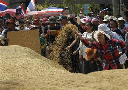 Farmers rearrange a pile of rice after they dumping them on the ground during a rally in Bangkok