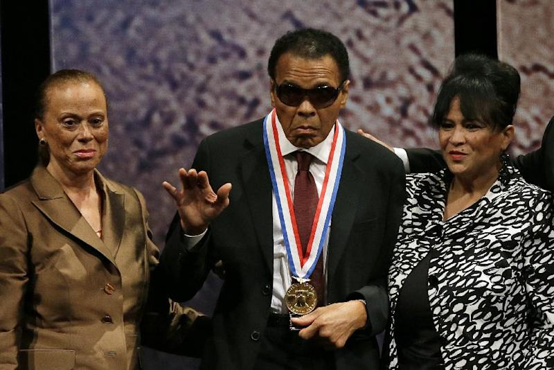 FILE - In this Sept. 13, 2012 file photo, boxing great Muhammad Ali, center, waves alongside his wife Lonnie Ali, left, and his sister-in-law Marilyn Williams, right, after receiving the Liberty Medal during a ceremony at the National Constitution Center in Philadelphia. Ali wants to recognize some of the greatest humanitarians around the world. The first-ever Muhammad Ali Humanitarian Awards will be presented Oct. 3 in Louisville, Ky. _ the former heavyweight champion's hometown. The Muhammad Ali Center said Tuesday, Aug. 27, 2013, that six awards will honor people ages 35 and under for making significant contributions for peace, social justice and other humanitarian causes. (AP Photo/Matt Slocum, File)