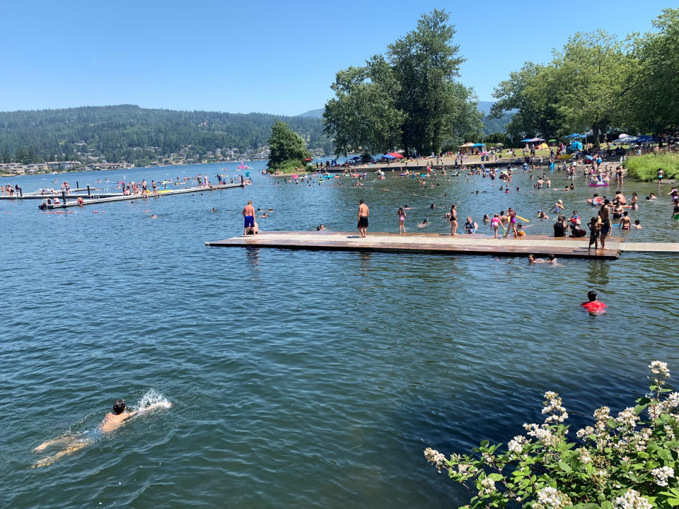 CORRECTS BYLINE TO LISA BAUMANN NOT CHRIS GRYGIEL People flock to Bloedel Donovan park at Lake Whatcom in Bellingham, Wash., during an uncharacteristic Pacific Northwest heat wave Sunday, June 26, 2021. Temperatures were expected to rise to 112 degrees in Portland, Oregon, on Sunday and 111 degrees at the Seattle-Tacoma International Airport on Monday. The heat wave was also moving into Idaho, where about 3,000 athletes were competing in an Ironman Triathlon in Coeur d'Alene. The event includes a 2.4 mile swim, a 112-mile bike ride and a 26.2-mile marathon run as temperatures top 100 degrees. (AP Photo/Lisa Baumann)