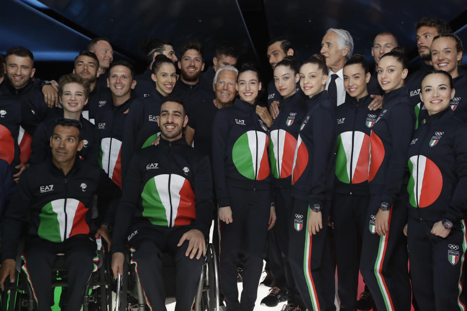 FILE - In this June 15, 2019 file photo, designer Giorgio Armani, centre, poses with Italian Olympic athletes at the end of the Emporio Armani men's Spring-Summer 2020 collection, unveiled during the fashion week, in Milan, Italy. Emporio Armani decked out Italy's team in track suits with a reinterpretation of Japan's rising sun in the colors of the country's flag: red, green and white.The Olympics in Tokyo open July 23, when the world's athletes will march behind their flag-bearers. (AP Photo/Luca Bruno)