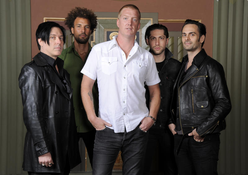 """In this May 23, 2013 photo, members of the band Queens of the Stone Age, from left, Troy Van Leeuwen, Jon Theodore, Josh Homme, Michael Shuman and Dean Fertita pose for a portrait at the Wiltern Theater, in Los Angeles. The band is releasing their first album in six years, """"... Like Clockwork,"""" on June 4. (Photo by Chris Pizzello/Invision/AP)"""