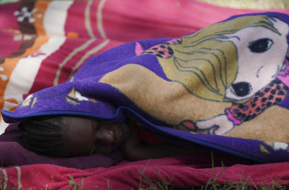 A migrant sleeps at an improvised refugee camp at a sport park in Ciudad Acuña, Mexico, Wednesday, Sept. 22, 2021. (AP Photo/Fernando Llano)