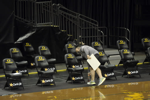 A member of the Oregon basketball staff clears the bench after the NCAA college basketball game between Oregon and UCLA cancelled, Wednesday, Dec. 23, 2020, at Matthew Knight Arena in Eugene, Ore. (AP Photo/Andy Nelson)