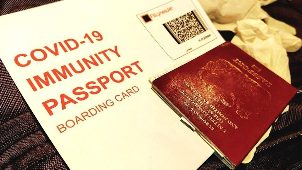 A mock-up of a Covid-19 Immunity passport boarding card, passport and gloves on a suitcase