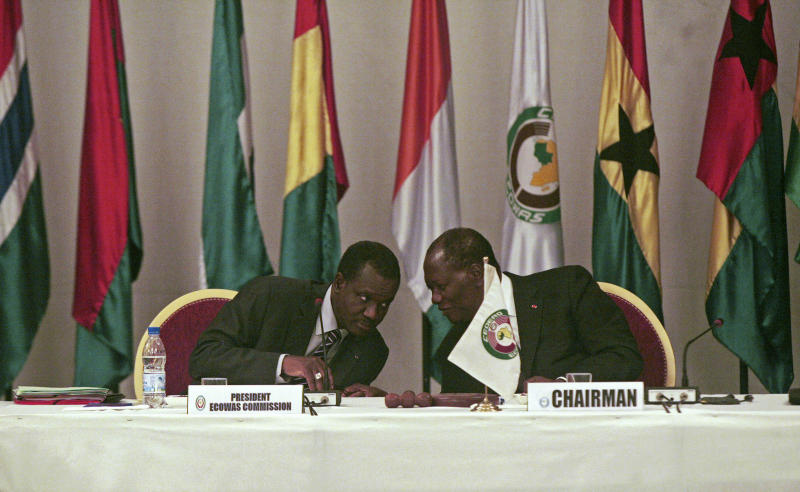 """Alassane Ouattara, right, the president of Ivory Coast who is the rotating chair of the Economic Community of West African States, consults with Kadre Desire Ouedraogo, the president of the ECOWAS commission, during an emergency meeting on Mali's recent military coup, in Abidjan, Ivory Coast Tuesday, March 27, 2012. The body representing nations in western Africa has suspended Mali and has put a peacekeeping force on standby in the most direct threat yet to the junta that seized control in a military coup last week. A delegation of five African presidents will head to Mali within the next 48 hours to try to """"restore constitutional order.""""(AP Photo/Emanuel Ekra)"""