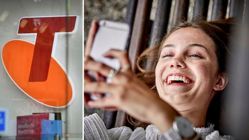 Telstra sign on the left and a smiling woman looking at her phone on the right.