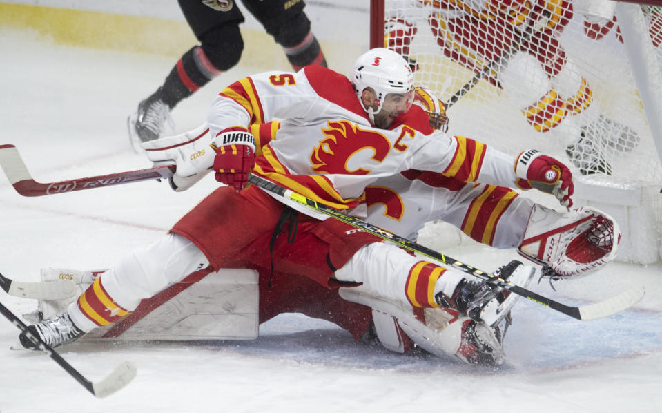 Calgary Flames defenseman Mark Giordano tries to help goaltender David Rittich stop a shot from Ottawa Senators right wing Drake Batherson during the first period of an NHL hockey game Thursday, Feb. 25, 2021, in Ottawa, Ontario. (Adrian Wyld/The Canadian Press via AP)