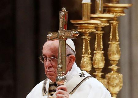 Pope Francis holds a cross as he conducts the Mass for the Feast of Epiphany in Saint Peter's Basilica at the Vatican