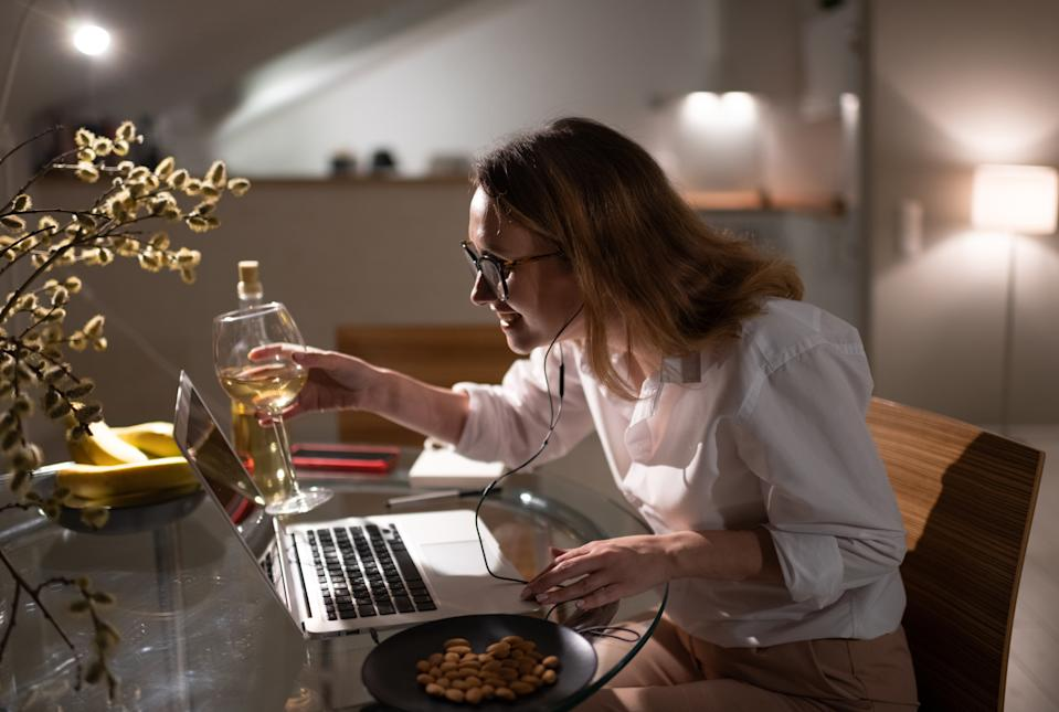 Side view of delighted young businesswoman in formal outfit sitting at table at home and clinking wineglass with virtual friends while having fun and communicating via laptop during quarantine because of coronavirus