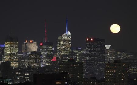 Moon rises behind the skyline of New York, as seen from Jersey City