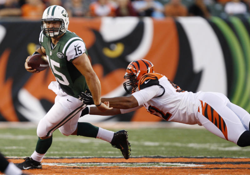 New York Jets quarterback Tim Tebow (15) avoids a tackle by Cincinnati Bengals defensive end Jamaal Anderson during the first half of an NFL preseason football game, Friday, Aug. 10, 2012, in Cincinnati. (AP Photo/David Kohl)