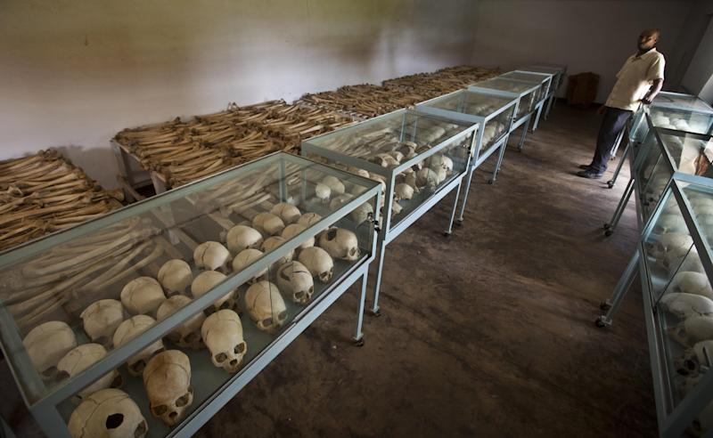 In this photo taken Thursday, March 27, 2014, Mike Nkuzumuwami stands by the rows of human skulls and bones that form a memorial to those who died in the redbrick church that was the scene of a massacre during the 1994 genocide, and which he helps to look after, in the village of Nyarubuye, eastern Rwanda. Rwandans gathered in the nearby town of Kirehe Thursday to watch the arrival of a small flame, symbolic fire traveling the country as Rwanda prepares to mark 20 years since ethnic Hutu extremists killed neighbors, friends and family during a three-month rampage of violence aimed at ethnic Tutsis and some moderate Hutus, the death toll of which Rwanda puts at 1,000,050. (AP Photo/Ben Curtis)