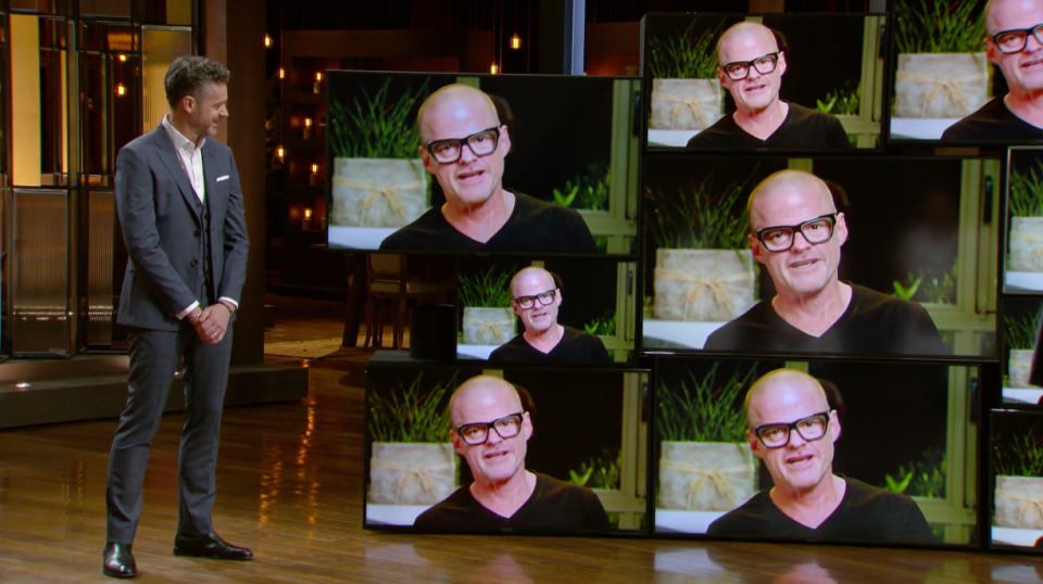 MasterChef judge Jock Zonfrillo stands next to a wall of televisions showing a video of Heston Blumenthal