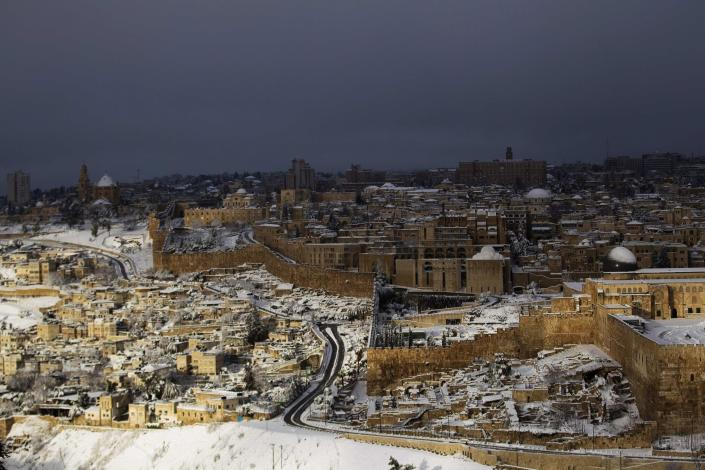 A view of Jerusalem's Old City (R) following a snowstorm is seen from the Mount of Olives February 20, 2015. Snow covered Jerusalem and mountainous areas of Israel early Friday morning and the education ministry closed schools for the day. (REUTERS/Ronen Zvulun)