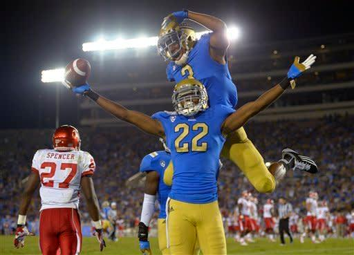 UCLA cornerback Sheldon Price, lower right, celebrates along with cornerback Randall Goforth after intercepting the ball as Houston wide receiver Daniel Spencer walks away during the second half of their NCAA college football game, Saturday, Sept. 15, 2012, in Pasadena, Calif. (AP Photo/Mark J. Terrill)