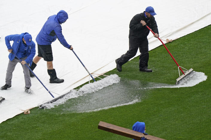 Groundskeepers remove water from a tarp as a baseball game between the New York Mets and the Atlanta Braves is postponed due to rain, Sunday, May 30, 2021, in New York. (AP Photo/Kathy Willens)