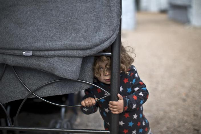 Refugee Moustafa Abdulrahman, 2, from Kobani, Syria, peeks out while standing outside his family's shelter at the refugee camp of Ritsona about 86 kilometers (53 miles) north of Athens, Thursday, Jan. 5, 2017. Over 62,000 refugees and migrants are stranded in Greece after a series of Balkan border closures and an European Union deal with Turkey to stop migrant flows. (AP Photo/Muhammed Muheisen)