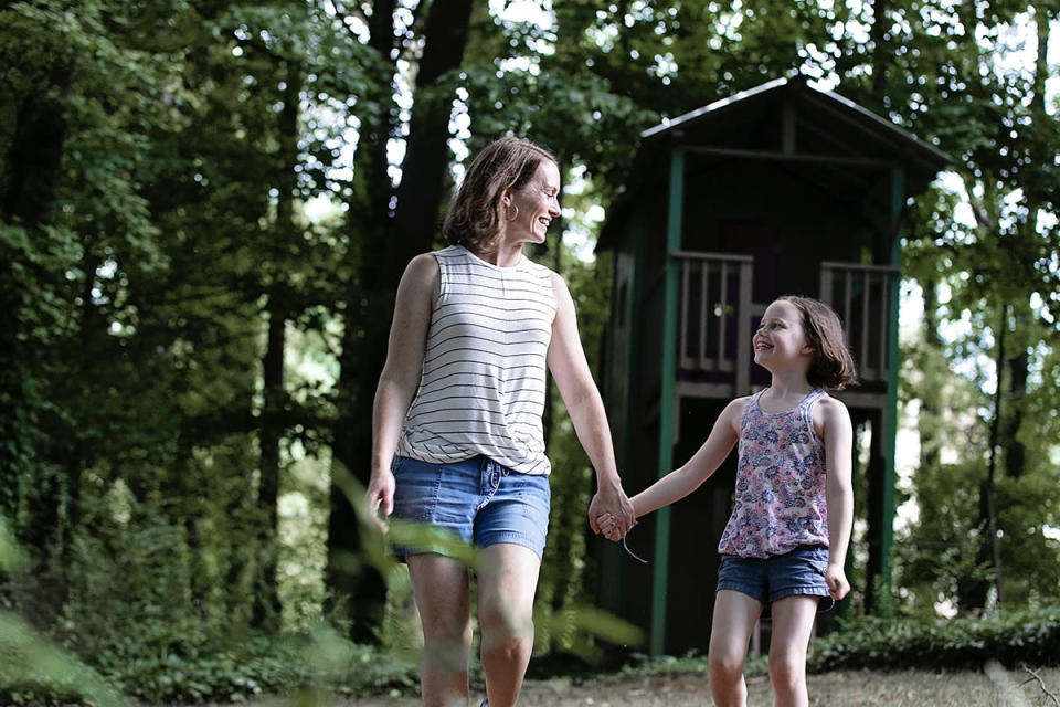 a woman and her daughter holding hands outside surrounded by trees.