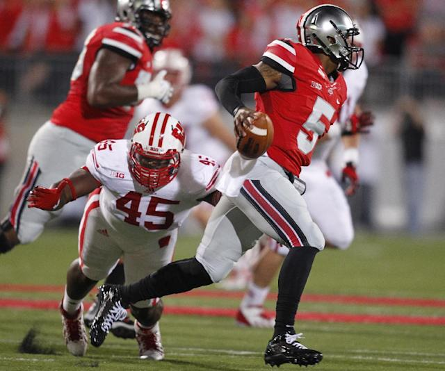 Ohio State quarterback Braxton Miller, right, escapes the grasp of Wisconsin defensive lineman Warren Herring during the first quarter of an NCAA college football game Saturday, Sept. 28, 2013, in Columbus, Ohio. Ohio State beat Wisconsin 31-24. (AP Photo/Paul Vernon)