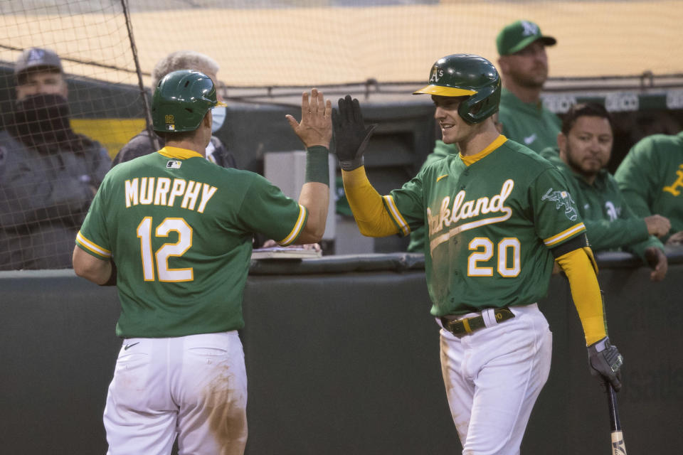 Oakland Athletics' Sean Murphy (12) celebrates with Mark Canha (20) after scoring a run against the Los Angeles Angels during the fifth inning of a baseball game in Oakland, Calif., Monday, June 14, 2021. (AP Photo/John Hefti)