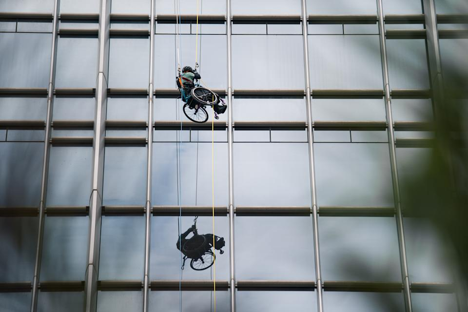 HONG KONG, CHINA - JANUARY 16: (EDITORIAL USE ONLY) Wheelchair Climber Lai Chi-wai completes 250-meter (75/f) out of 320-meter during his attempt to climb the 89-storey Nina Tower in Tsuen Wan by using only his upper body strength. The challenge raised over HK$5 million for spinal cord patients to utilize exoskeletons on January 16, 2021 at Nina Tower skyscraper, in Tsuen Wan, Hong Kong, China. (Photo by Lampson Yip - Clicks Images/Getty Images)