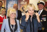 Britain's Camilla, Duchess of Cornwall (FRONT R) is watched by actress Barbara Windsor (FRONT L) as she speaks on the telephone at the annual ICAP charity day in the City of London December 3, 2013. REUTERS/Paul Grover/Pool (BRITAIN - Tags: ENTERTAINMENT BUSINESS SOCIETY ROYALS)