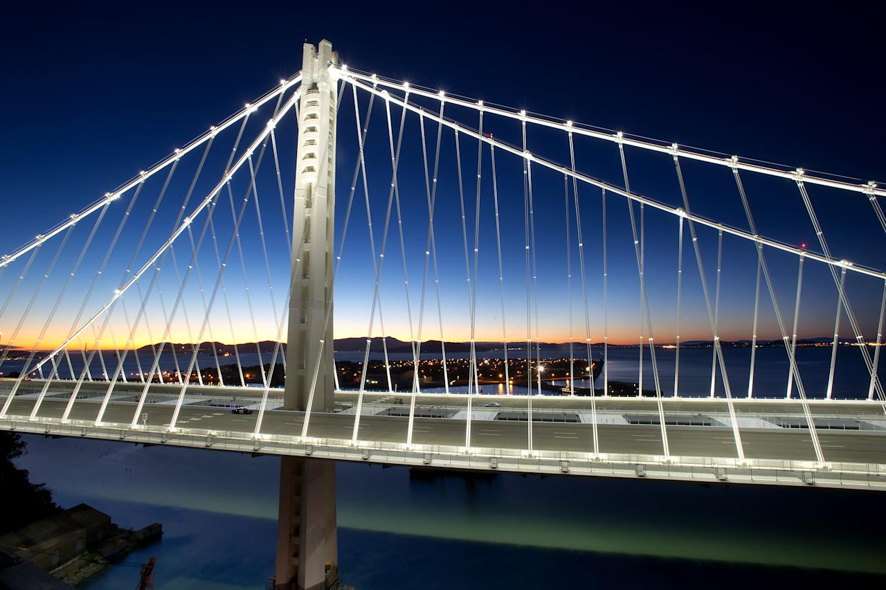 In a handout photo provided by the Bay Area Toll Authority, LED lights illuminate the San Francisco-Oakland Bay Bridge's self-anchored suspension on Thursday, Aug. 29, 2013, in San Francisco. With traffic between Oakland and San Francisco halted over Labor Day weekend for construction, bridge officials say the new span will open by Tuesday morning. (AP Photo/Noah Berger)