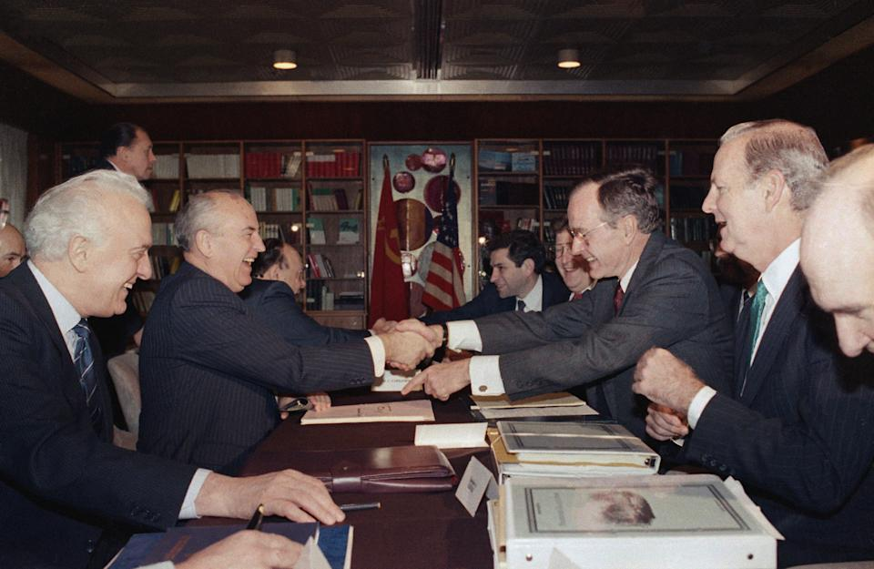 USSR President Mikhail Gorbachev and U.S. President George H. W. Bush clasp hands at a bilateral meeting in December 1989. Soviet Foreign Minister Eduard Shevardnadze, left, and Baker, as U.S. secretary of states, right, look on.