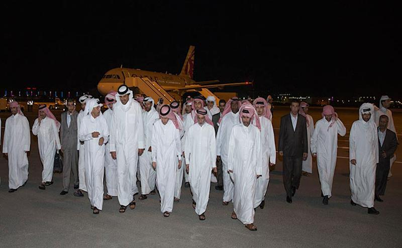 In this photo released by Qatar News Agency, Emir of Qatar Sheikh Tamim bin Hamad Al Thani, second left in front row, receives the released Qataris at the Doha airport in Doha, Qatar Friday, April 21, 2017. After nearly a year and a half in captivity, Qatar on Friday secured the release of 26 hostages, including members of its ruling family, in what became possibly the region's most complex and sensitive hostage negotiation deal in recent years. (Qatar News Agency via AP)