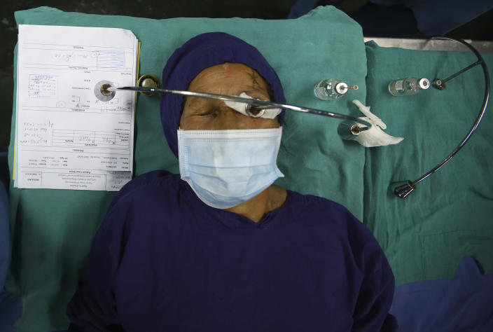 """A patient lies on a hospital bed after receiving anesthesia before cataract surgery at the Tilganga Eye Center in Kathmandu, Nepal, March 26, 2021. Nepal's """"God of Sight"""" eye doctor renowned for his innovative and inexpensive cataract surgery for the poor is taking his work beyond the Himalayan mountains to other parts of the world so there is no more unnecessary blindness in the world. Dr. Sanduk Ruit, who has won many awards for his work and performed some 130,000 cataract surgery in the past three decades, is aiming to expand his work beyond the borders of his home country and the region to go globally. (AP Photo/Niranjan Shrestha)"""