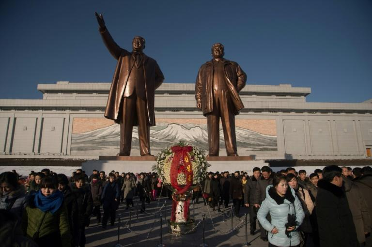 People lay flowers at the statues of late North Korean leaders Kim Il-Sung (L) and Kim Jong-Il to mark the sixth anniversary of the death of Kim Jong-Il, in Pyongyang