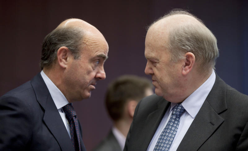 Spain's Economy Minister Luis de Guindos, left, speaks with Irish Finance Minister Michael Noonan during a meeting of  eurogroup finance ministers in Brussels on Monday, March 4, 2013. The eurogroup finance ministers are set to discuss details of a bailout for cash-strapped Cyprus, further steps of assistance for Portugal and Ireland as well as the controversial issue of direct banking recapitalizations through Europe's permanent rescue fund. (AP Photo/Virginia Mayo)