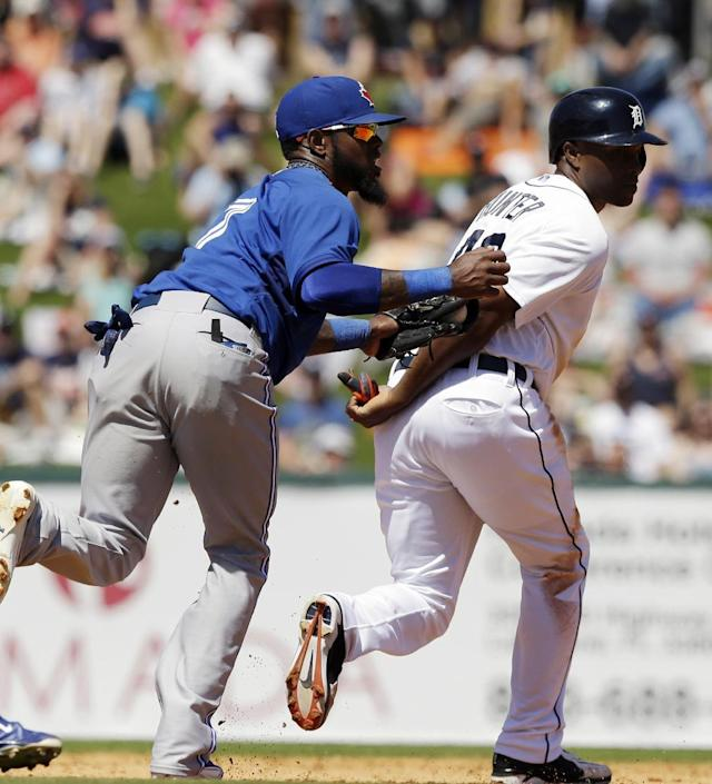 Detroit Tigers right fielder Torii Hunter, right, is tagged out by Toronto Blue Jays shortstop Jose Reyes on a rundown between second and third during the third inning of a spring exhibition baseball game in Lakeland, Fla., Tuesday, March 18, 2014. (AP Photo/Carlos Osorio)