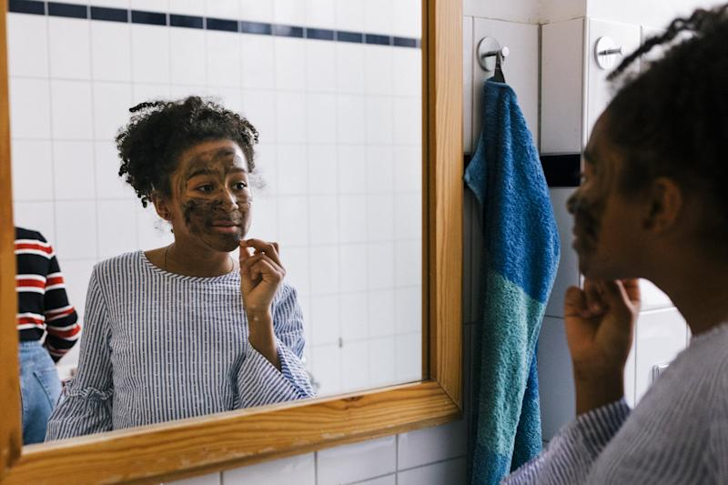 Black tween in applying facial mask while looking into a bathroom mirror.