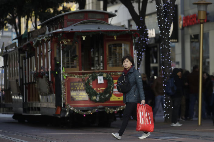 FILE - In this Nov. 29, 2019, file photo a woman carries a shopping bag while walking in front of a cable car in San Francisco. Holiday shopping doesn't end with Christmas. Bargain hunters can take advantage of fatter discounts on clothing, home decor and other items between Christmas and well into January. (AP Photo/Jeff Chiu, File)