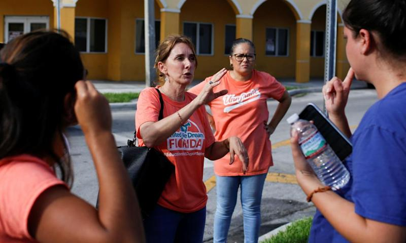 Immigration rights activists talk in Miami, during an event to hand out pamphlets as communities brace for a reported wave of Ice raids.