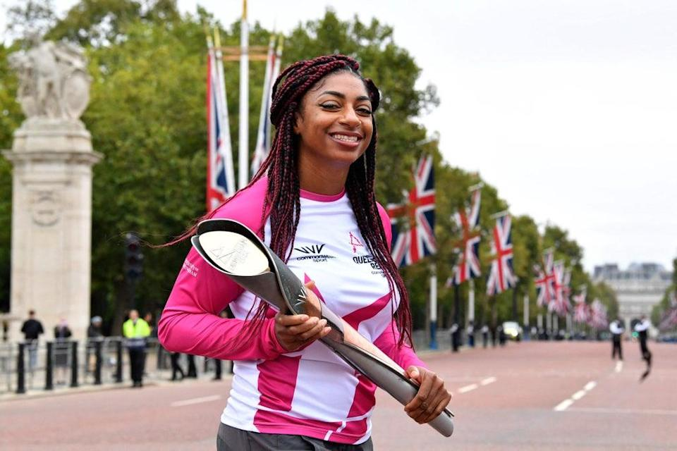 Double Paralympic gold medallist Kadeena Cox carries the baton (AFP via Getty Images)