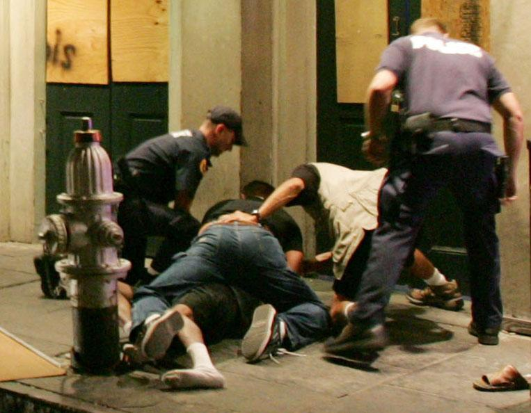 FILE - In this Oct. 8, 2005 file photo, police officers subdue a man on Conti Street near Bourbon Street in the French Quarter of New Orleans. At least one police officer repeatedly punched 64-year-old Robert Davis, accused of public intoxication, and another officer assaulted an Associated Press Television News producer as a cameraman taped the confrontations. Attorney General Eric Holder will announce Tuesday, July 24. 2012 a series of court-supervised reforms of the New Orleans Police Department that are some of the broadest and strictest ever imposed on a law-enforcement agency. The agreement between the Justice Department and the city is designed to clean up a police force that has been plagued by decades of corruption and mismanagement and came under renewed scrutiny after Hurricane Katrina struck in 2005. (AP Photo/Mel Evans, File)