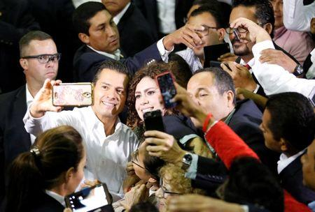 Mexican President Enrique Pena Nieto takes a selfie with supporters of the Institutional Revolutionary Party (PRI) during their national assembly ahead of the 2018 election at Mexico City's Palacio de los Deportes, Mexico August 12, 2017. REUTERS/Henry Romero
