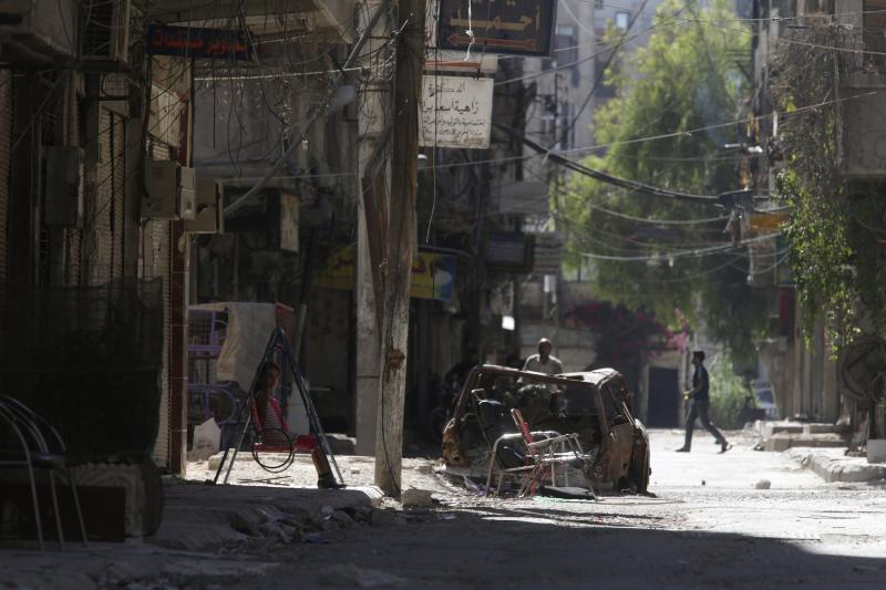 A girl rests on swing along a damaged street in Ain Tarma, in Eastern Ghouta, a suburb of Damascus