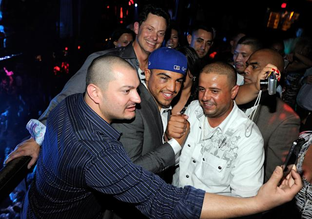 LAS VEGAS, NV - SEPTEMBER 18: (EXCLUSIVE COVERAGE) Boxer Victor Ortiz (C) takes photos with fans as he appears at a post-fight party at Studio 54 inside the MGM Grand Hotel/Casino early on September 18, 2011 in Las Vegas, Nevada. Ortiz lost the WBC welterweight title to Floyd Mayweather Jr. by fourth-round knockout on September 17. (Photo by Ethan Miller/Getty Images for Studio 54)