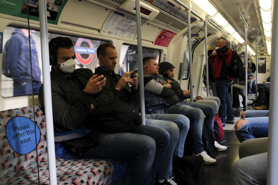 Commuters, some wearing protective masks to protect against coronavirus travel on a Jubilee Line underground train, in London, Monday, May 18, 2020. Britain's Prime Minister Boris Johnson announced last Sunday that people could return to work if they could not work from home. (AP Photo/Alberto Pezzali)
