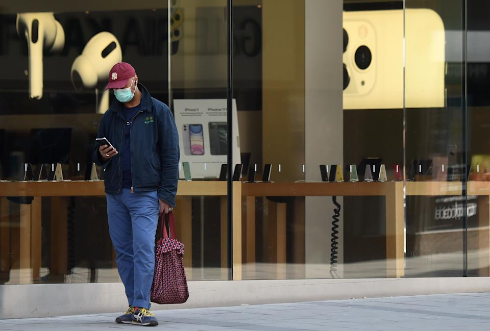 A man wearing a face mask walks past a closed electronic goods store in the center of Munich, southern Germany, on April 9, 2020 as public life in Bavaria has been limited due to the coronavirus COVID-19. (Photo by Christof STACHE / AFP) (Photo by CHRISTOF STACHE/AFP via Getty Images)