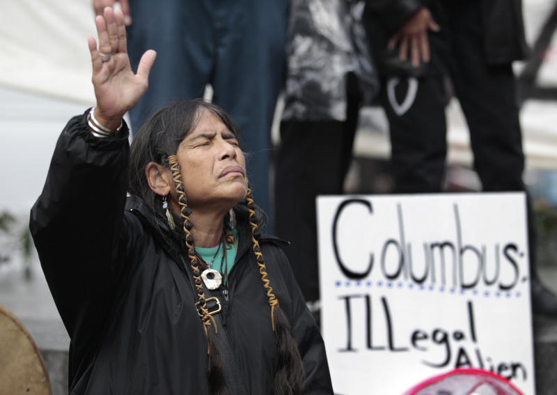 """FILE - In this Monday, Oct. 10, 2011 file photo, Ferntree, of Duncan, British Columbia, a member of the Cowichan Tribes, holds her hand up as a prayer is given during a Native American protest against Columbus Day in Seattle. Protest organizers say that Columbus could not have """"discovered"""" a western hemisphere already inhabited by about 100 million people. (AP Photo/Elaine Thompson)"""