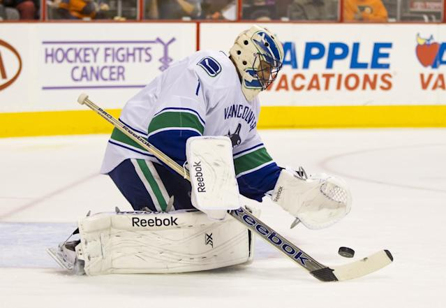 Vancouver Canucks' Roberto Luongo looks to cover up the loose puck during the second period of an NHL hockey game against the Philadelphia Flyers, Tuesday, Oct. 15, 2013, in Philadelphia. (AP Photo/Chris Szagola)